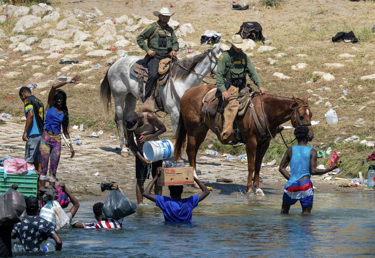 U.S. Border Patrol agents interact with Haitian immigrants on the bank of the Rio Grande in Del Rio, Texas, on Monday, Sept. 20, 2021, as seen from Ciudad Acuna, Mexico. (John Moore/Getty Images/TNS)