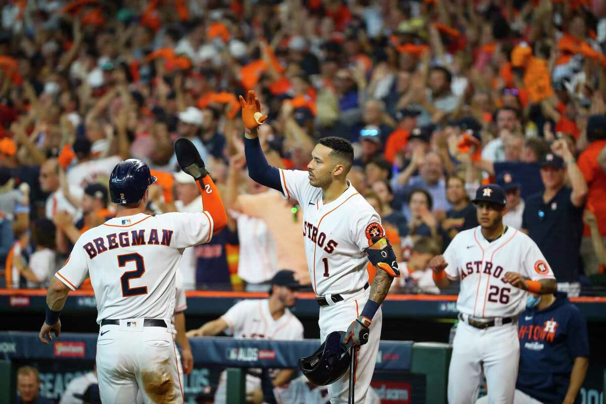 Houston Astros third baseman Alex Bregman (2) is welcomed back to the dugout by Houston Astros shortstop Carlos Correa (1) after Bregman was driven home by a double by Houston Astros designated hitter Yordan Alvarez (44) during the third inning in Game 1 of the AL Division Series Thursday, Oct. 7, 2021, in Houston.