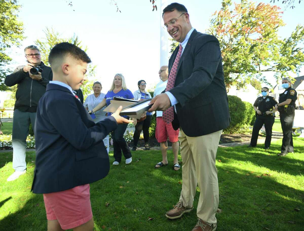 Make a Wish recipient Anthony Muoio, 7, of Milford, receives a proclamation from Mayor Ben Blake during a city ceremony and WPLR radio interviews on The Green in Milford, Conn. on Thursday, October 7, 2021. For his wish, Muoio, a brain tumor survivor, will receive a camper for his family.