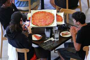 A customer snaps a picture of a pizza just brought to the table during the grand opening of Sally's Apizza on Summer Street in Stamford, Conn., on Thursday October 7, 2021. This is the new outpost of the beloved New Haven pizza restaurant.