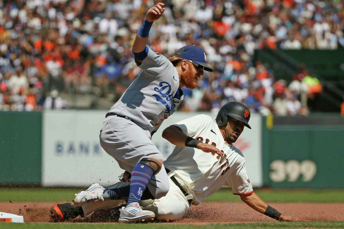 Los Angeles Dodgers third baseman Justin Turner (10) tags out the San Francisco Giants' LaMonte Wade Jr (31) as they collide in the seventh inning during an MLB game at Oracle Park, Thursday, July 29, 2021, in San Francisco, Calif.