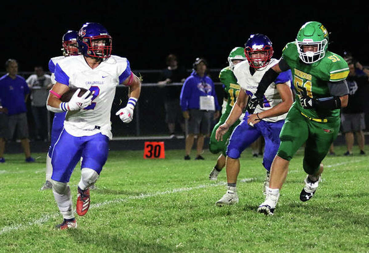 Carlinville wide receiver Carson Wiser (left) carries the football with Southwestern's Aaron Frost (right) giving chase during Friday's game in Piasa.