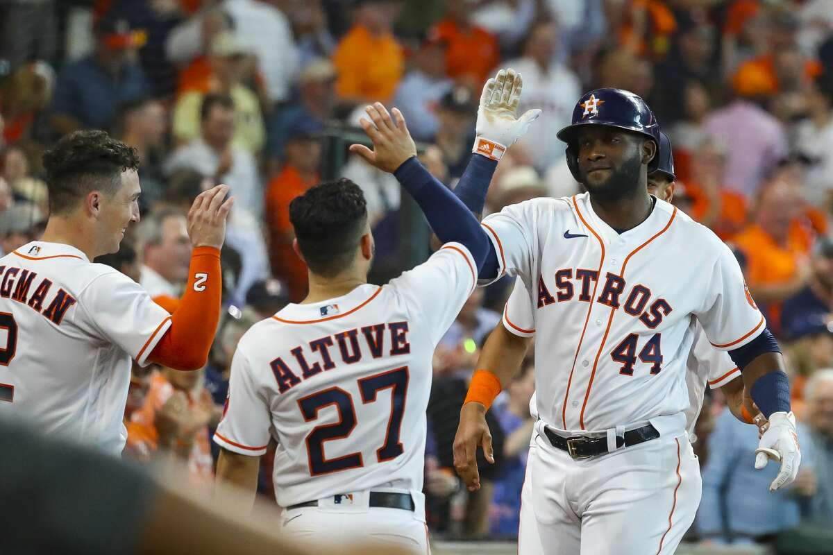 Houston Astros designated hitter Yordan Alvarez (44) is welcomed back to the dugout by Houston Astros third baseman Alex Bregman (2) and Houston Astros second baseman Jose Altuve (27) after hitting a solo home run to give the Astros a 6-0 lead during the fifth inning in Game 1 of the AL Division Series Thursday, Oct. 7, 2021, in Houston.