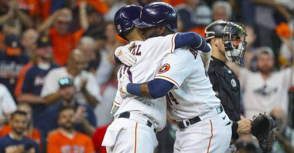 Houston Astros first baseman Yuli Gurriel (10) hugs Houston Astros designated hitter Yordan Alvarez (44) after Alvarez hit a solo home run to start the fifth inning in Game 1 of the AL Division Series Thursday, Oct. 7, 2021, in Houston.