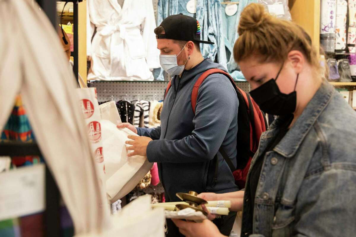 Breanna Miller and Brennan Stokes of San Francisco wear masks while shopping inside Cliff's Variety on Castro Street in San Francisco. Mask rules for vaccinated people entering San Francisco stores will probably not be lifted for a few months.