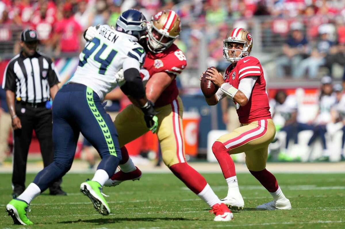 San Francisco 49ers quarterback Jimmy Garoppolo drops back to pass as offensive tackle Mike McGlinchey (69) blocks Seattle Seahawks defensive end Rasheem Green (94) an NFL football game in Santa Clara, Calif., Sunday, Oct. 3, 2021. (AP Photo/Tony Avelar)