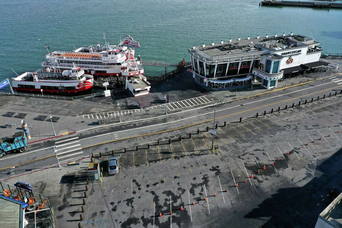 A parking lot next to a restaurant and bay cruise terminal at Fisherman's Wharf tourist destination sits empty at the start of the coronavirus pandemic in March 2020.