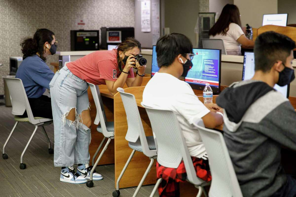 Ranger photographer Veronica Alcorta, from left, photographs Steven Saavedra and his friend Alejandro Velasquez as they work on homework in the San Antonio College Writing Center on Wednesday. The Ranger is set to close in December after 95 years. Alcorta started working for it a week ago.