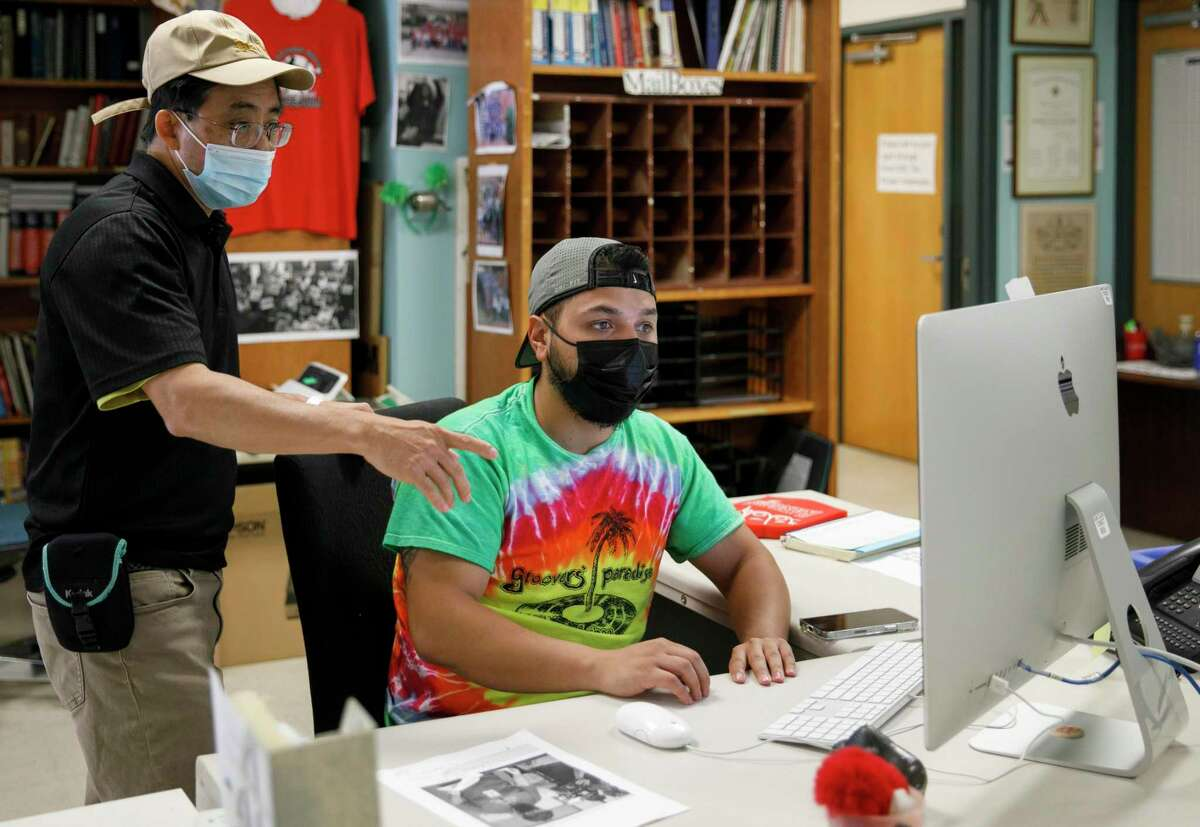 Journalism professor Edmund Lo, left, helps Rocky Garza Jr. edit a photo caption Wednesday in The Ranger newsroom at San Antonio College.  Garza is the editor.  The 95-year-old student publication will cease operations at the end of the semester.