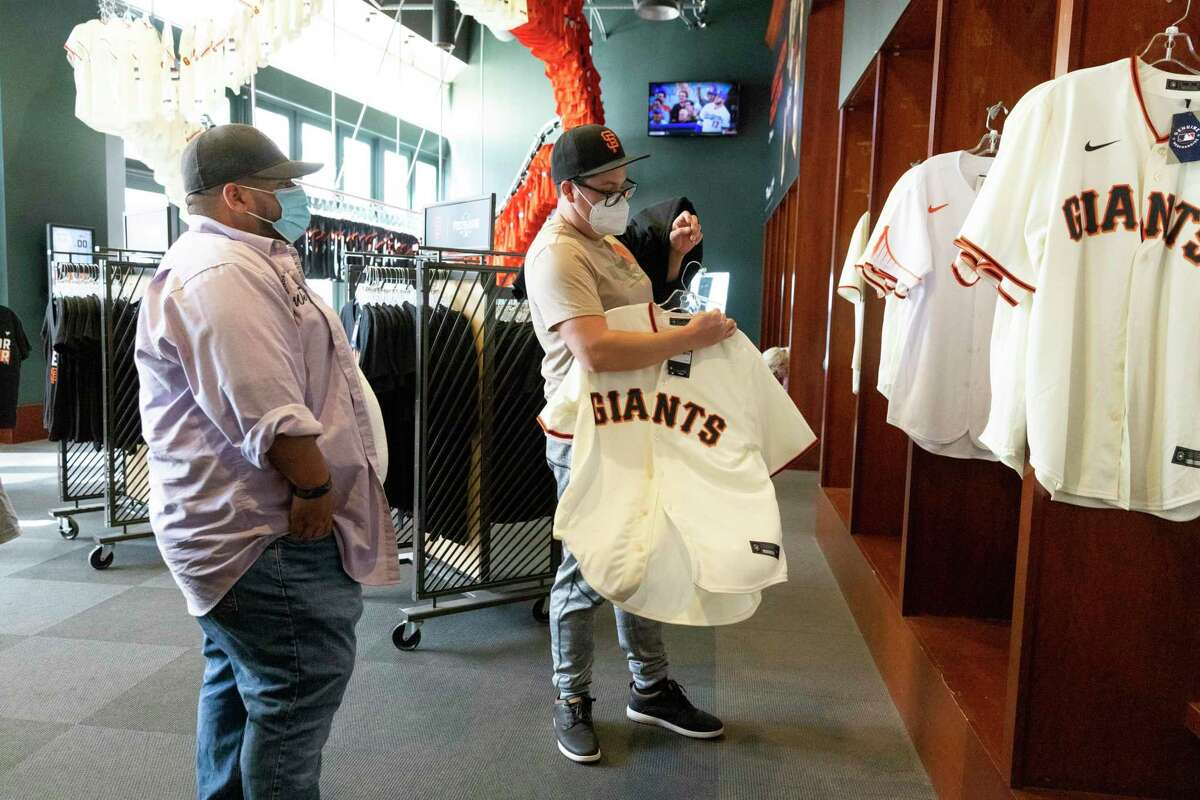 Rudy Paredes (left) and Mario Alvarado shop for gear at the Giants Dugout Store at Oracle Park in San Francisco. The Giants will face the Dodgers in Game 1 of the NDLS on Friday night.