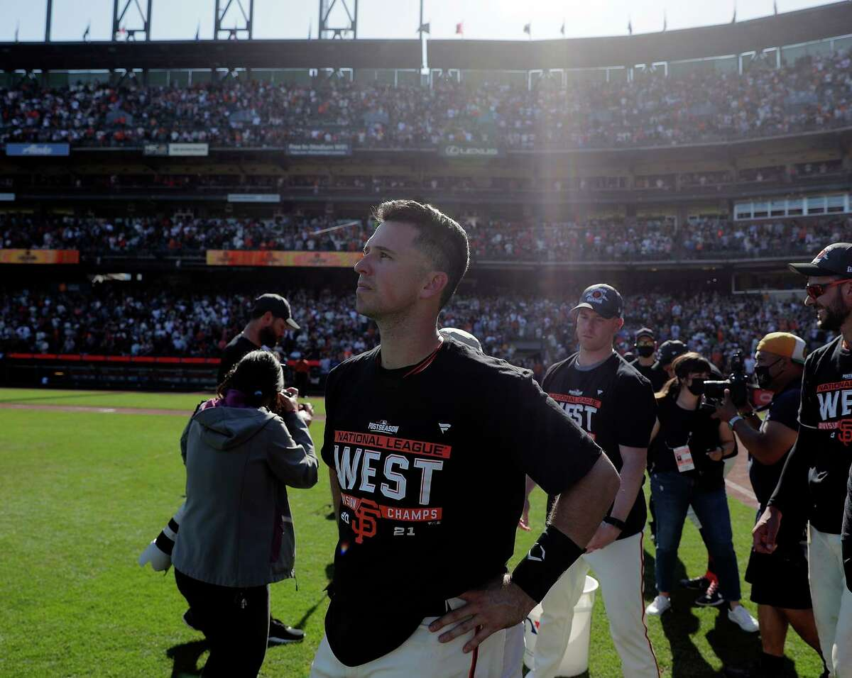 Buster Posey stops to take it in as the San Francisco Giants celebrate on the field after they defeated the San Diego Padres 11-4 to win the National League West at Oracle Park in San Francisco, Calif., on Sunday, October 3, 2021.