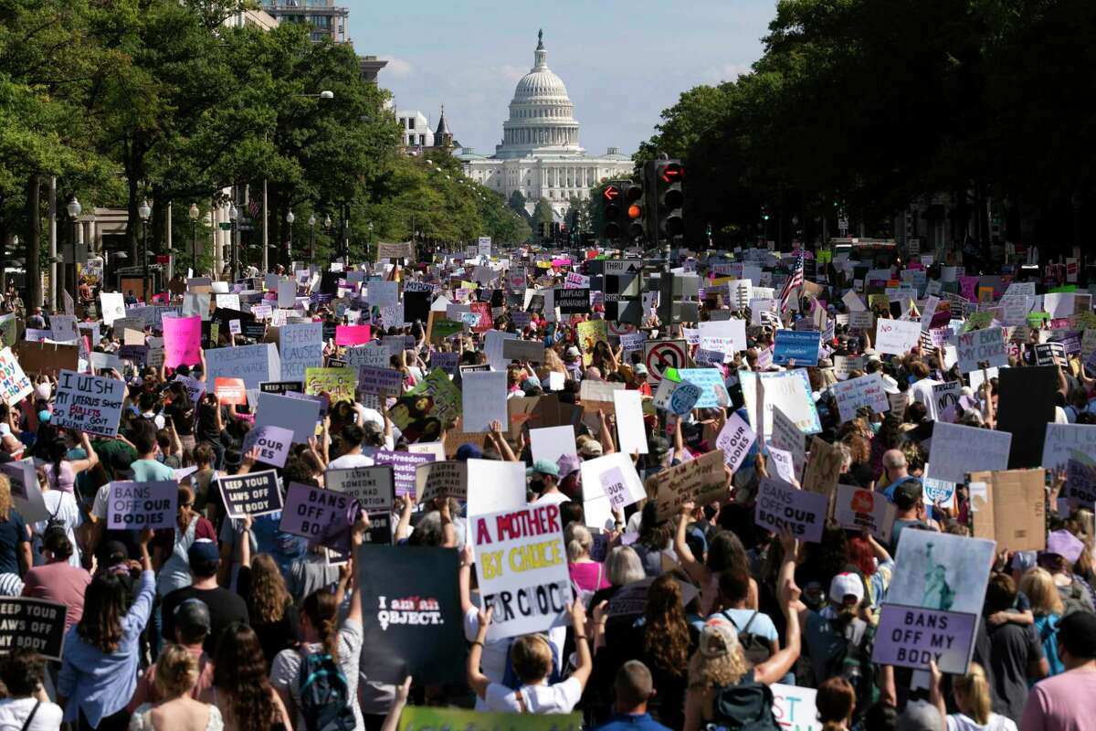 With the U.S Capitol in the background, thousands of demonstrators march on Pennsylvania Avenue during the Women's March in Washington, D.C., Saturday, Oct. 2, 2021.
