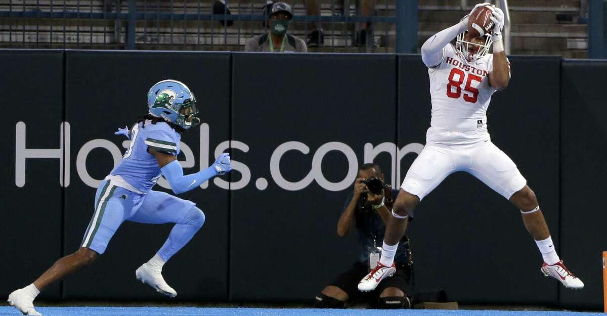 Wide open Houston tight end Christian Trahan (85) catches the ball in the end zone for a touchdown before Tulane defensive back Ajani Kerr (21) can make a play on the ball during an NCAA college football game in New Orleans, Thursday, Oct. 7, 2021. (A.J. Sisco/The Advocate via AP)