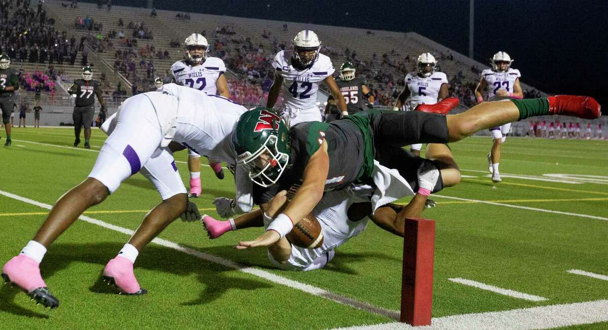 The Woodlands quarterback Mabrey Mettauer (11) dives for a 8-yard touchdown during the first quarter of a District 13-6A high school football game at Woodforest Bank Stadium, Thursday, Oct. 7, 2021, in Shenandoah.