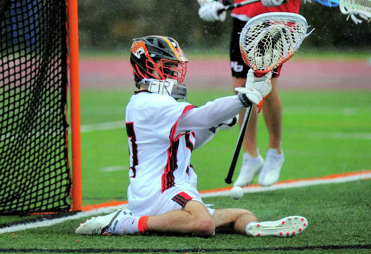 Ridgefield goalie Matthew Shepard (17) deflects a New Canaan ball during boys lacrosse action in Ridgefield in April.