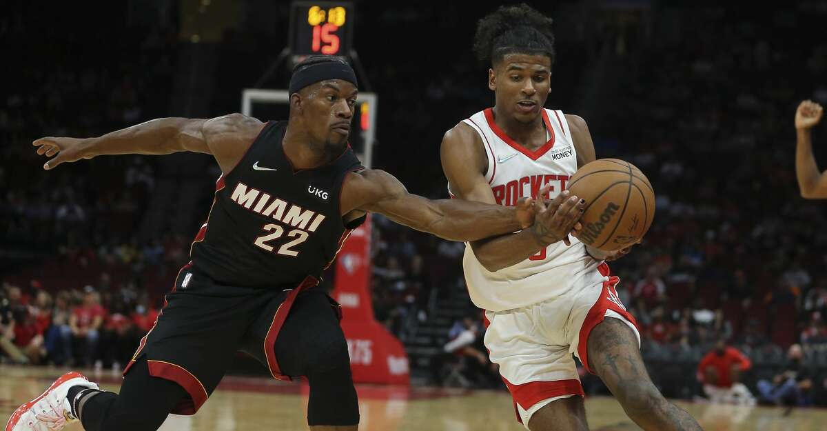 Miami Heat forward Jimmy Butler (22) strips the ball from Houston Rockets guard Jalen Green (0) during the first quarter of a NBA preseason game Thursday, Oct. 7, 2021, at Toyota Center in Houston.