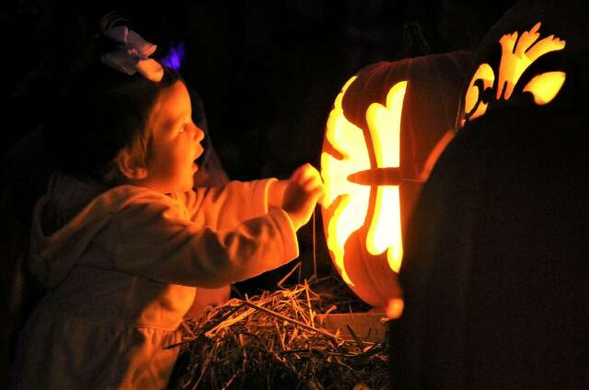 A small child gets up close and personal to an illuminated, carved pumpkin on the opening day of Pumpkins in the City, part of the Harvest Festival at Silver Dollar City in Branson, Missouri. The festival continues through Oct. 30.