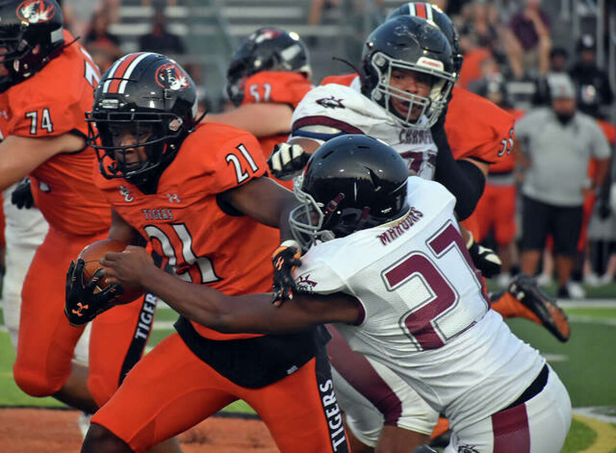 Edwardsville running back Jordan Bush stiff arms a Champaign Central defender during a game earlier this season inside the District 7 Sports Complex.