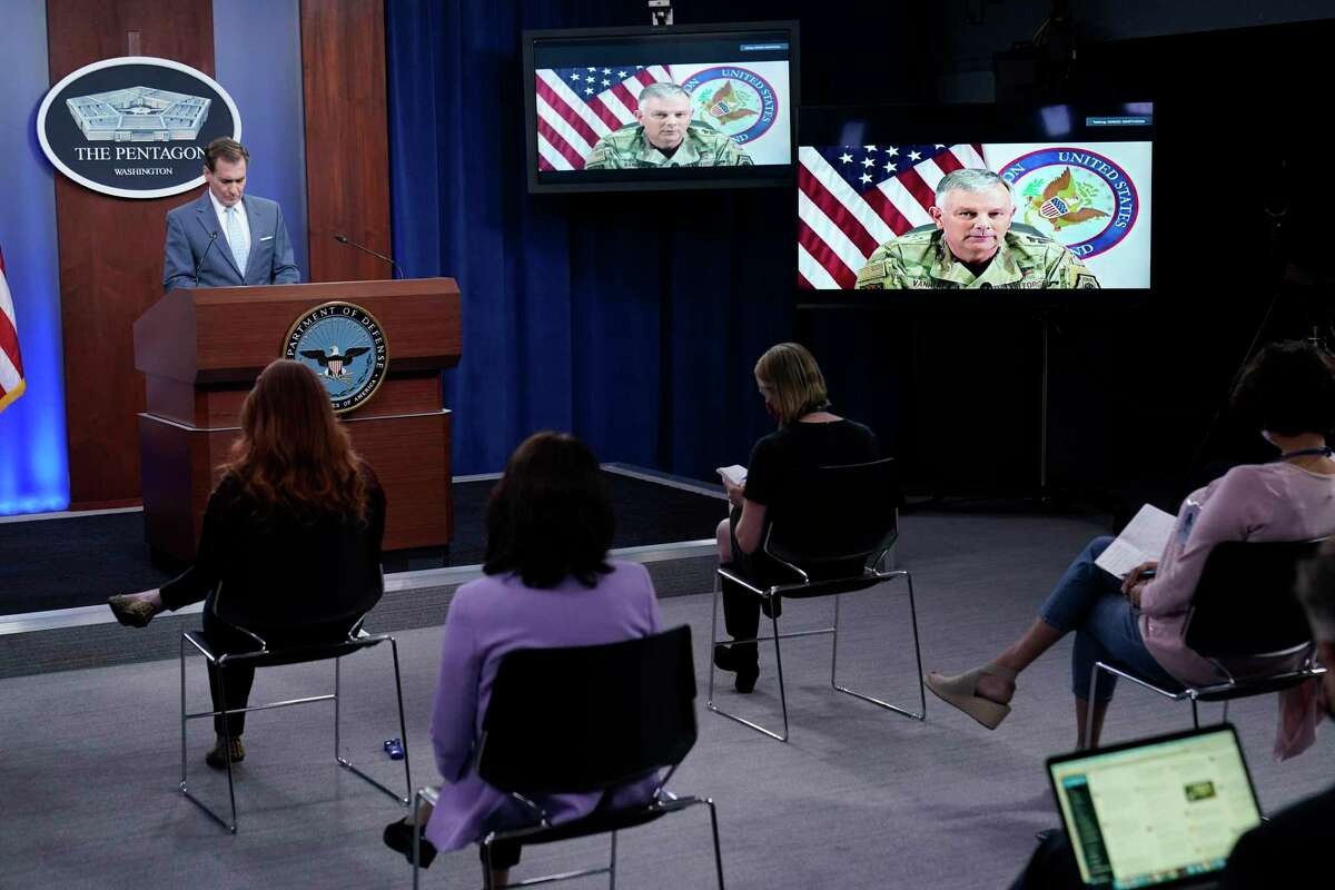 Pentagon spokesman John Kirby, left, listens as Air Force Gen. Glen D. VanHerck, commander of U.S. Northern Command and the North American Aerospace Defense Command, on screen, speaks during a briefing at the Pentagon in Washington, Thursday, Sept. 30, 2021. (AP Photo/Susan Walsh)