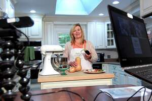Susan Doyle, who uses Zoom to broadcast her show: Downsized Gourmet, poses in her kitchen at her home in Stamford, Conn., on Tuesday October 5, 2021. Due to the COVID-19 pandemic, in June of 2020 Susan and her husband Paul, who takes care of all things tech related, started the cooking show and invited members of several senior centers and facilities to tune in. Their work has culminated in a cookbook which will raise money for the Fairfield County Walk to End Alzheimer's slated for Sunday October 10th.
