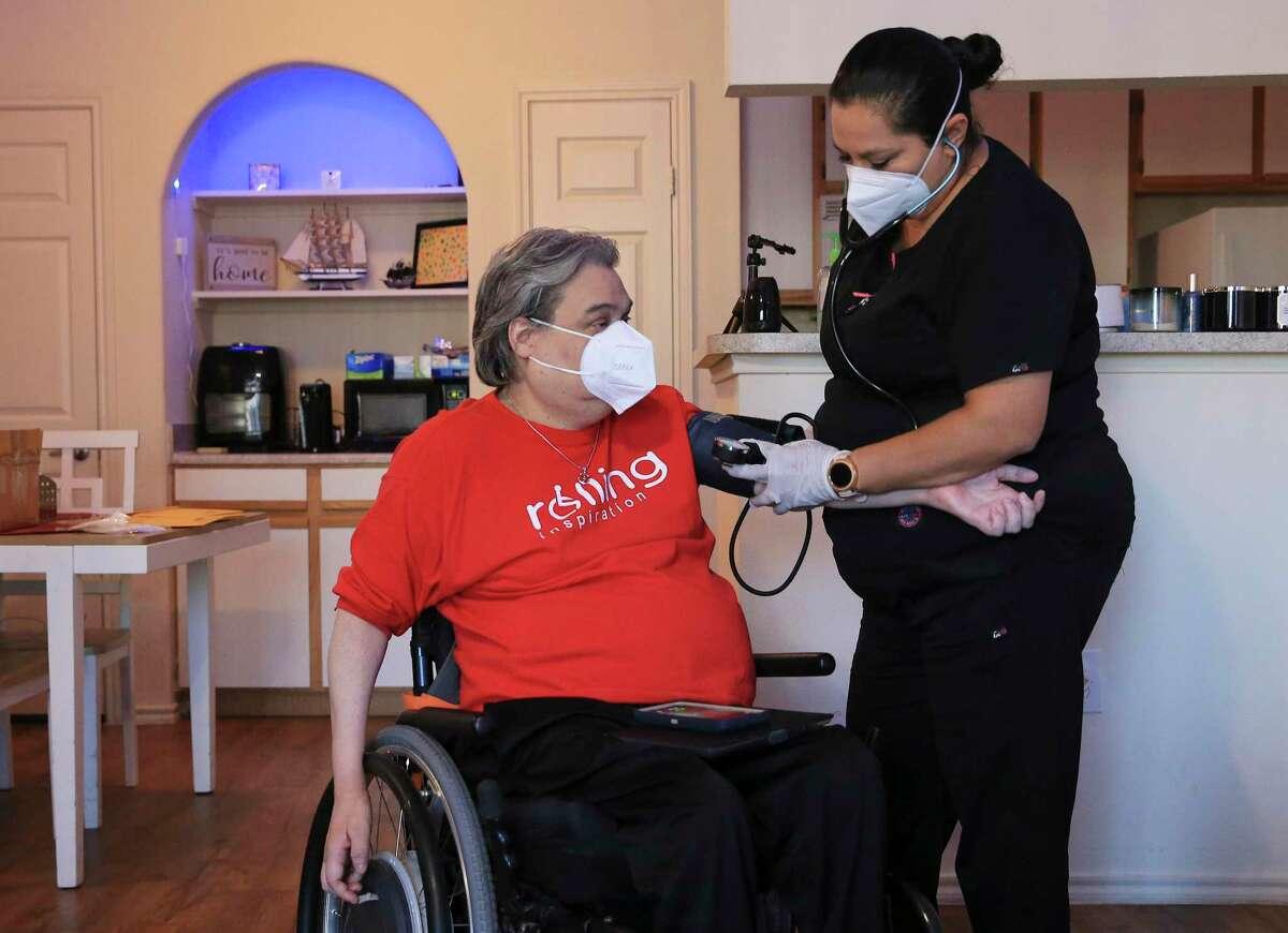Nurse Yolanda Torres checks the vitals for Chris Salas.