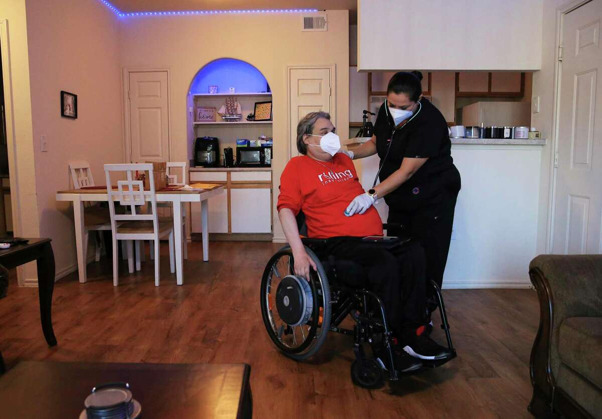 """Nurse Yolanda Torres checks the vitals for Chris Salas. After being paralyzed in a car accident in 1997, Salas founded Rolling Inspiration, a local nonprofit with a goal of """"helping all people with mobility impairments."""""""