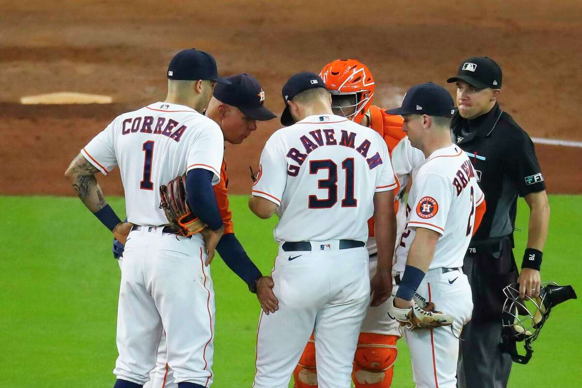Houston Astros pitching coach Brent Strom (56) talks with Houston Astros relief pitcher Kendall Graveman (31) during the eighth inning in Game 1 of the AL Division Series Thursday, Oct. 7, 2021, in Houston.