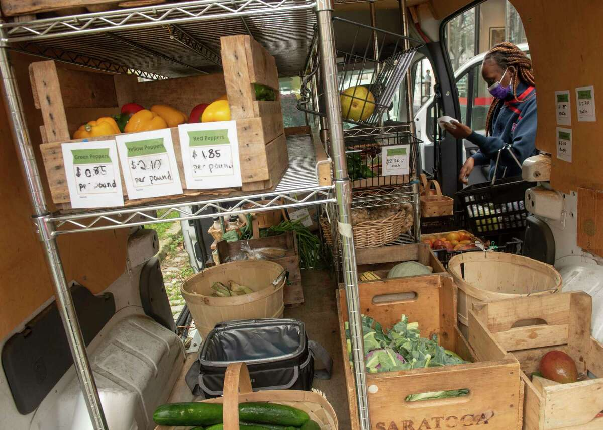Jeanne Sinzinkayo, from U.S. Committee for Refugees and Immigrants in Albany, shops for produce from one of the Capital Roots Veggie Mobiles parked at Jim DiNapoli Park on Friday, Oct, 8, 2021 in Albany, N.Y. She was filling an order from someone who was texting what they wanted.