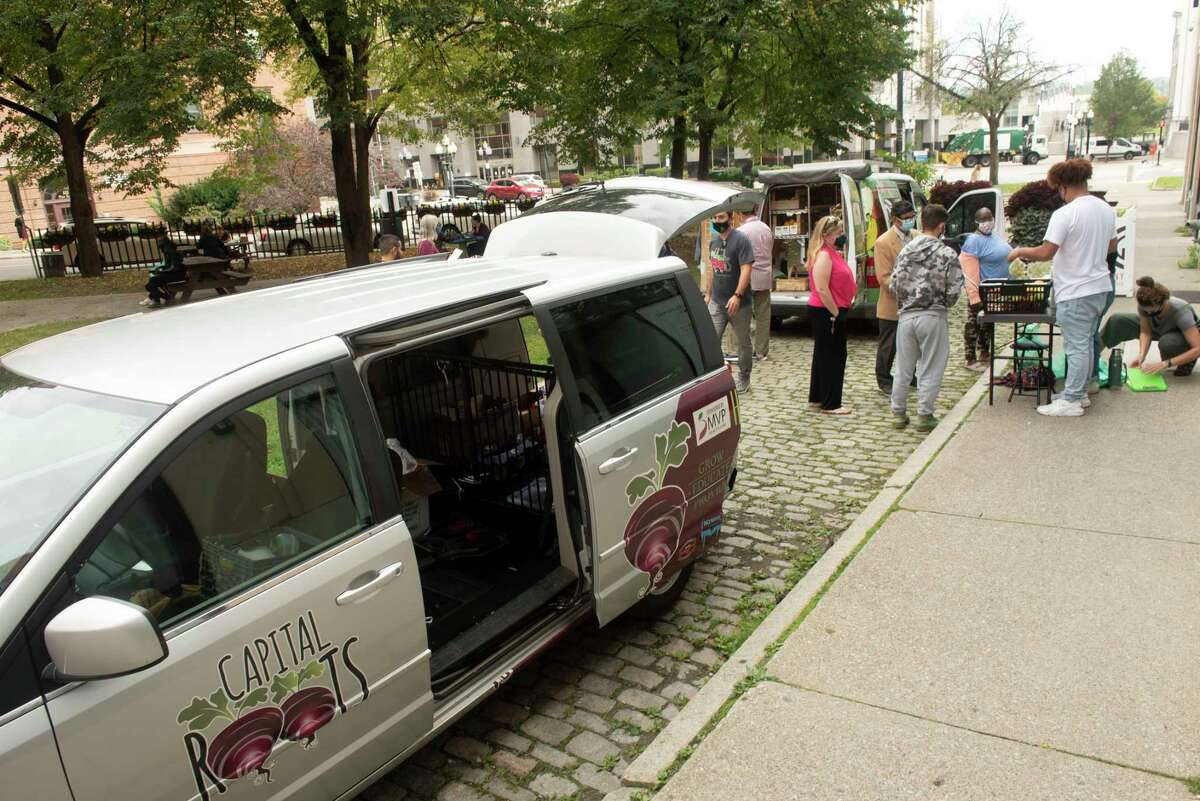 People shop for produce from one of the Capital Roots Veggie Mobiles parked at Jim DiNapoli Park on Friday, Oct, 8, 2021 in Albany, N.Y.