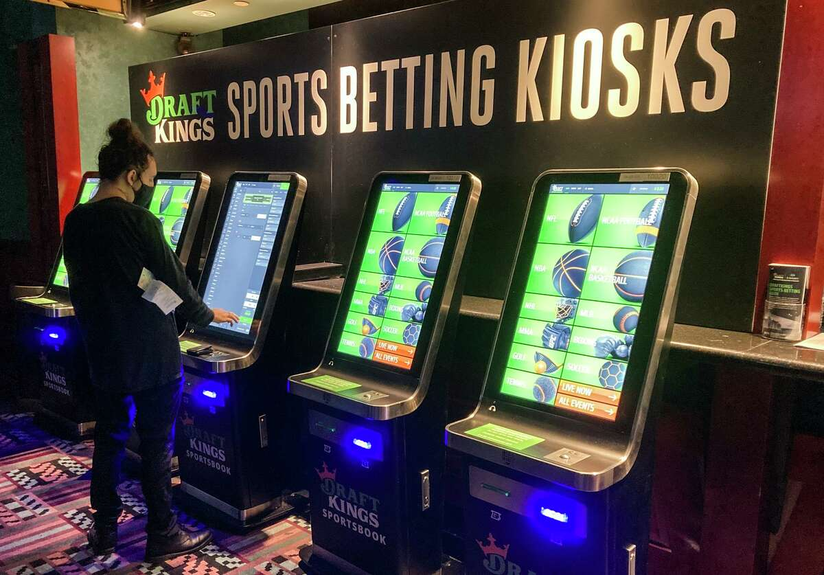 """Zach Young, of New Haven, places a bet at one of the new sports wagering kiosks at Foxwoods Resort Casino in Mashantucket on Sept. 30. Young says he's been """"waiting for this day,"""" recalling how he'd often scroll through sports betting apps he couldn't play in preparation. The unveiling of temporary sports betting venues at the state's two tribal casinos, Foxwoods and Mohegan Sun, mark the first step in the rollout of Connecticut's new law legalizing sports and online wagering. (AP Photo/Susan Haigh)"""