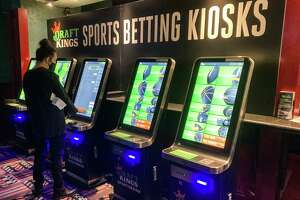 """Zach Young, of New Haven, Conn., places a bet at one of the new sports wagering kiosks at Foxwoods Resort Casino in Mashantucket, Conn., Thursday, Sept. 30, 2021. Young says he's been """"waiting for this day,"""" recalling how he'd often scroll through sports betting apps he couldn't play in preparation. The unveiling of temporary sports betting venues at the state's two tribal casinos, Foxwoods and Mohegan Sun, mark the first step in the rollout of Connecticut's new law legalizing sports and online wagering. (AP Photo/Susan Haigh)"""