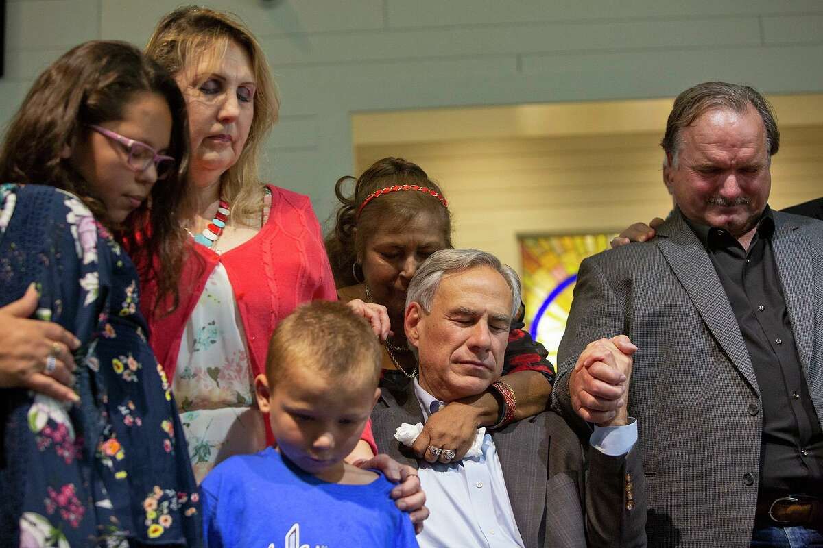 Shooting survivors including Rihanna Tristan, from left, Julie Workman, Ryland Ward, Farida Brown, with Governor Greg Abbott, and David Colbath join together in prayer during the dedication ceremony for the new building for First Baptist Church of Sutherland Springs on Sunday, May 19, 2019.