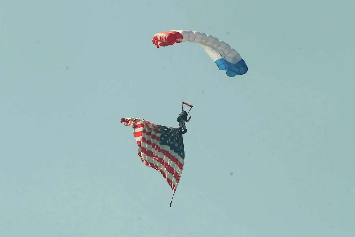 A member of the Re/Max Skydive Team delivers the American flag to open the show.