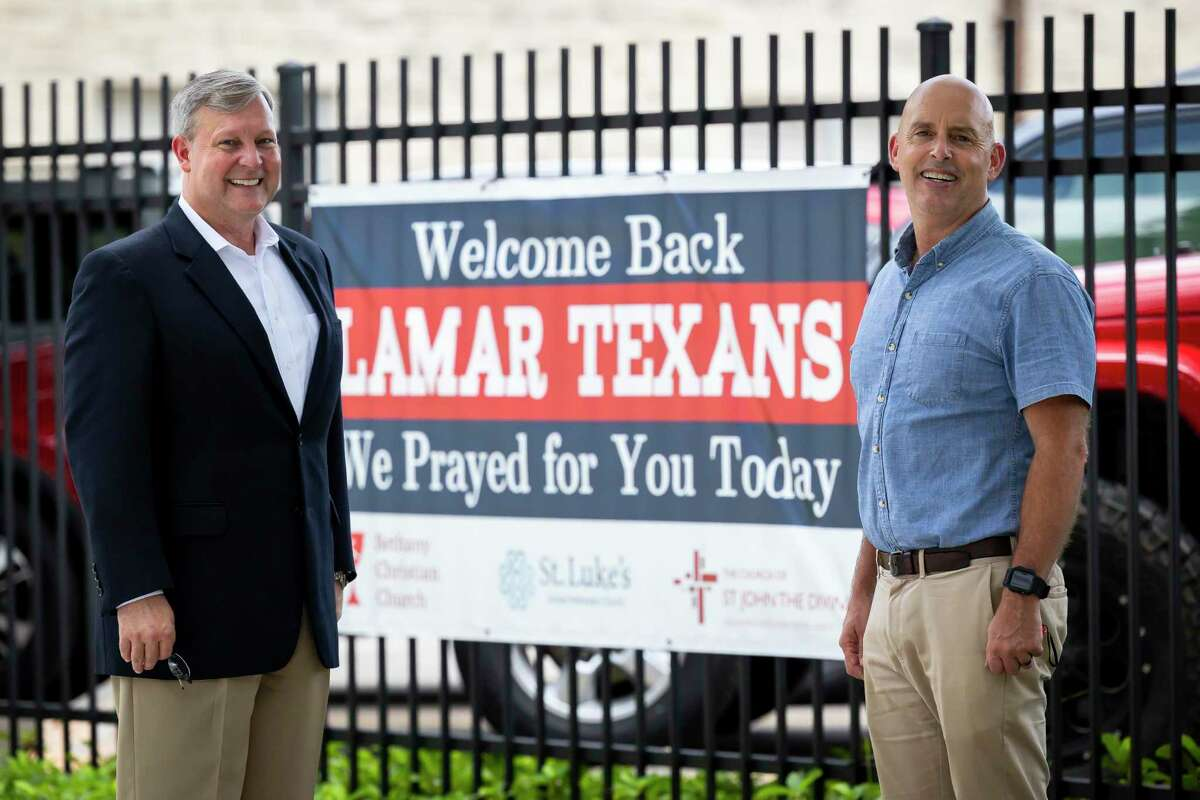 The Church of St. John the Divine lay leader Larry Lawyer and family minister Dan Gannon pose in front of a sign outside of Lamar High School on Friday, Sept. 2, 2021. In January 2020, Lawyer started Loving Lamar, an initiative to support wraparound care for students who attend Lamar High School.