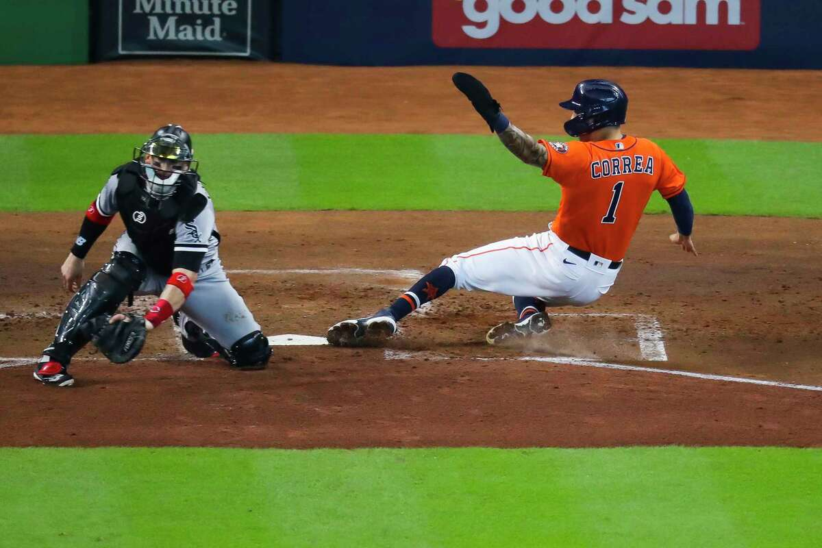 Houston Astros shortstop Carlos Correa (1) slides past Chicago White Sox catcher Yasmani Grandal (24) to score on a sacrifice fly by Houston Astros left fielder Chas McCormick (20) during the second inning in Game 2 of the American League Division Series on Friday, Oct. 8, 2021, at Minute Maid Park in Houston.