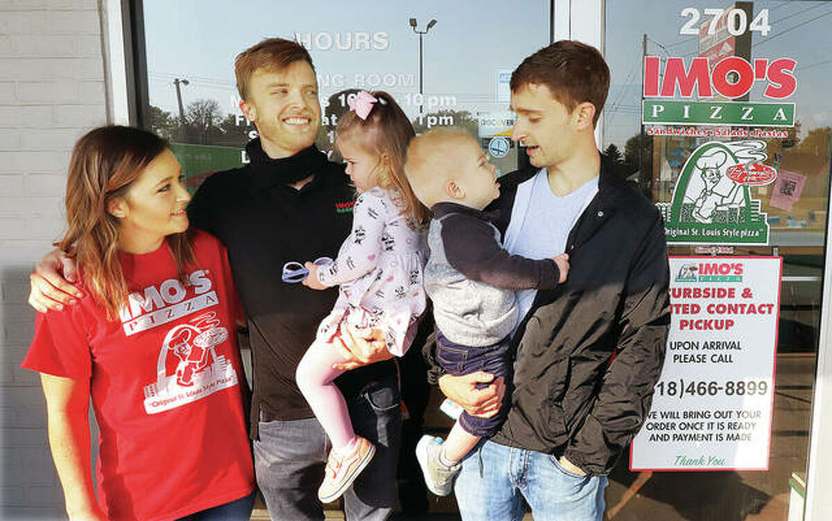 Hayden and Tyler Shereck, left, last year with their children, Ava, now 3, and Luke, now 2, along with Imo's Pizza co-owner Thomas Shereck, right, after a fire destroyed their Imo's restaurant last year. Nearly one year to the day, they have rebuilt and reopened at the same location at 2704 Godfrey Road, in Alton.