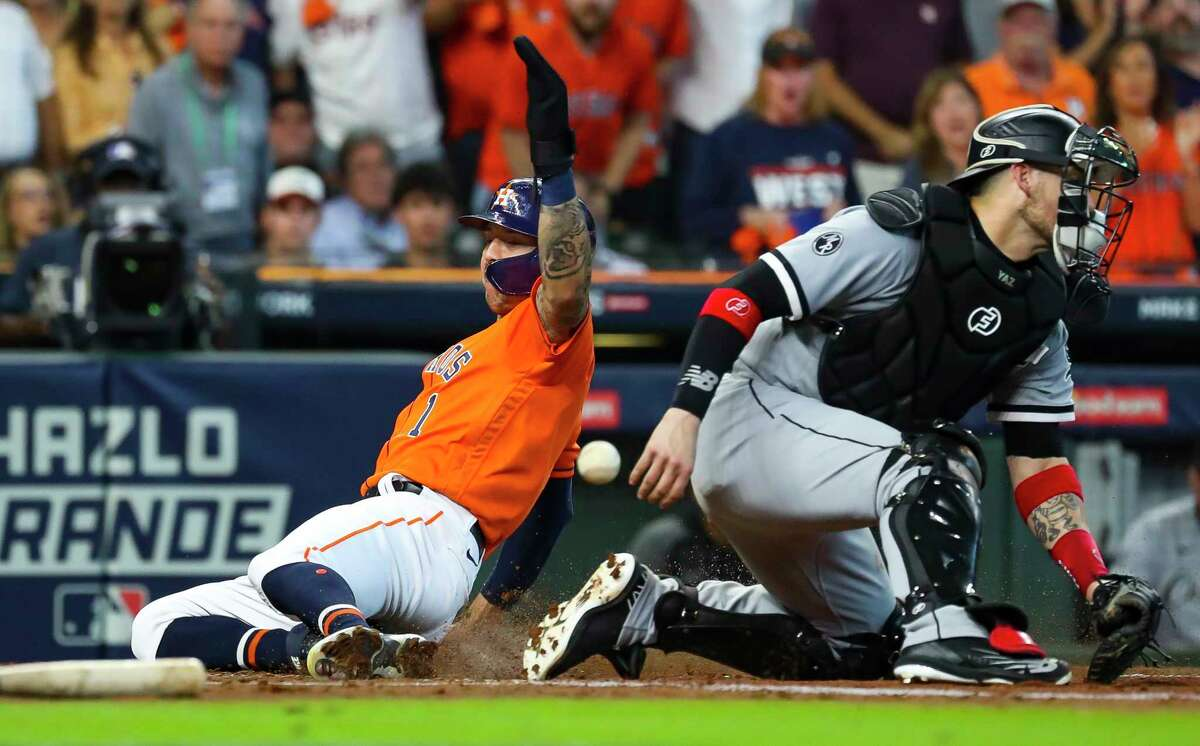 Houston Astros shortstop Carlos Correa (1) beats the throw to Chicago White Sox catcher Yasmani Grandal (24) at home to score on a sacrifice fly by Houston Astros left fielder Chas McCormick (20) and give the Astros a 2-1 lead during the second inning in Game 2 of the American League Division Series on Friday, Oct. 8, 2021, at Minute Maid Park in Houston.