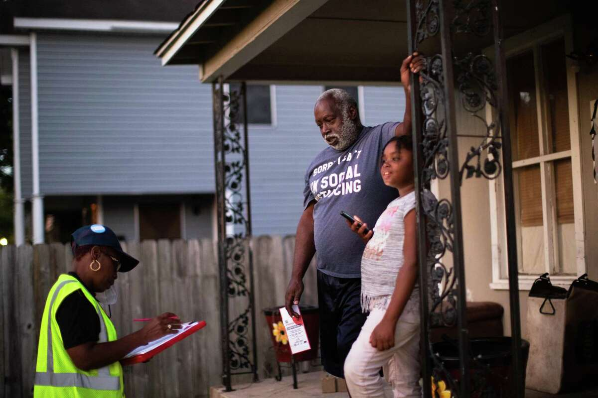 Coalition of Community Organizations block captain Sandra Edwards, left, fills information about the home of Willie Holman, right, so the house can get inspected for lead, Thursday, Oct. 7, 2021, in Houston.