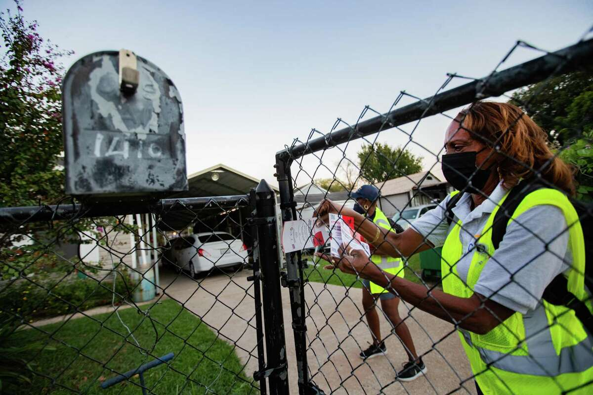 Coalition of Community Organizations block captain Cookie Straughter places a flyer with information about how homes at Fifth Ward are at risk of having lead painting while doing her rounds, Thursday, Oct. 7, 2021, in Houston.