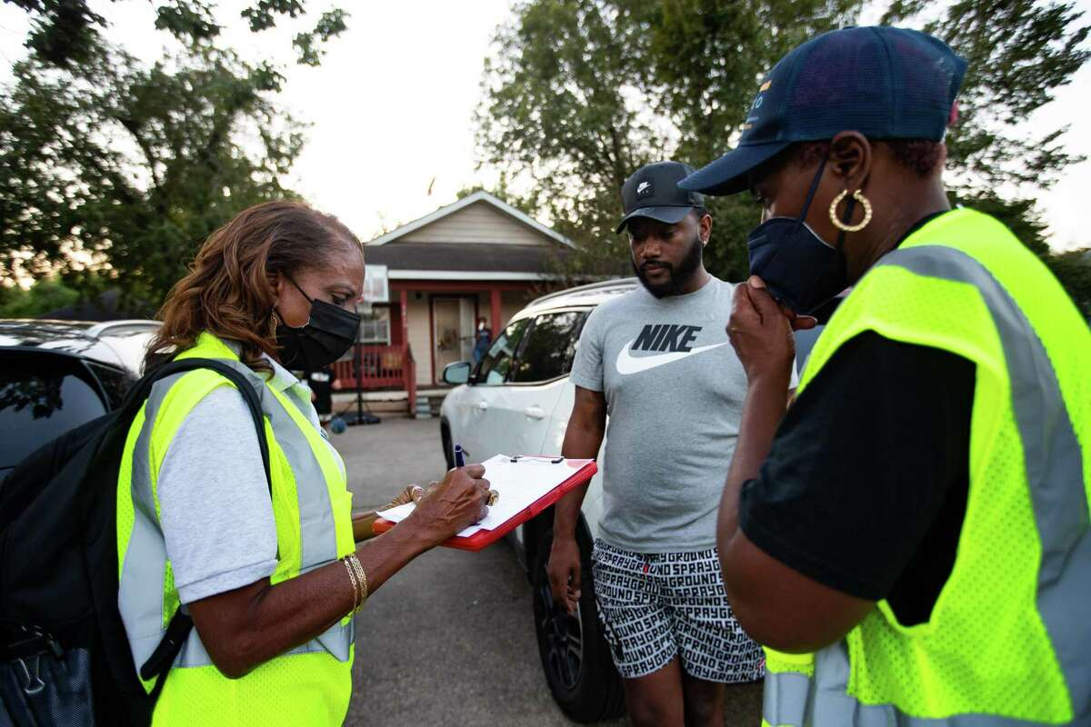 Coalition of Community Organizations block captain Cookie Straughter, left, fills information provided by Xavier Calhoun, 29, about the home of his aunt which might have lead, Thursday, Oct. 7, 2021, in Houston. The home is located at Fifth Ward which is an area that has been identified with homes exposed with lead.