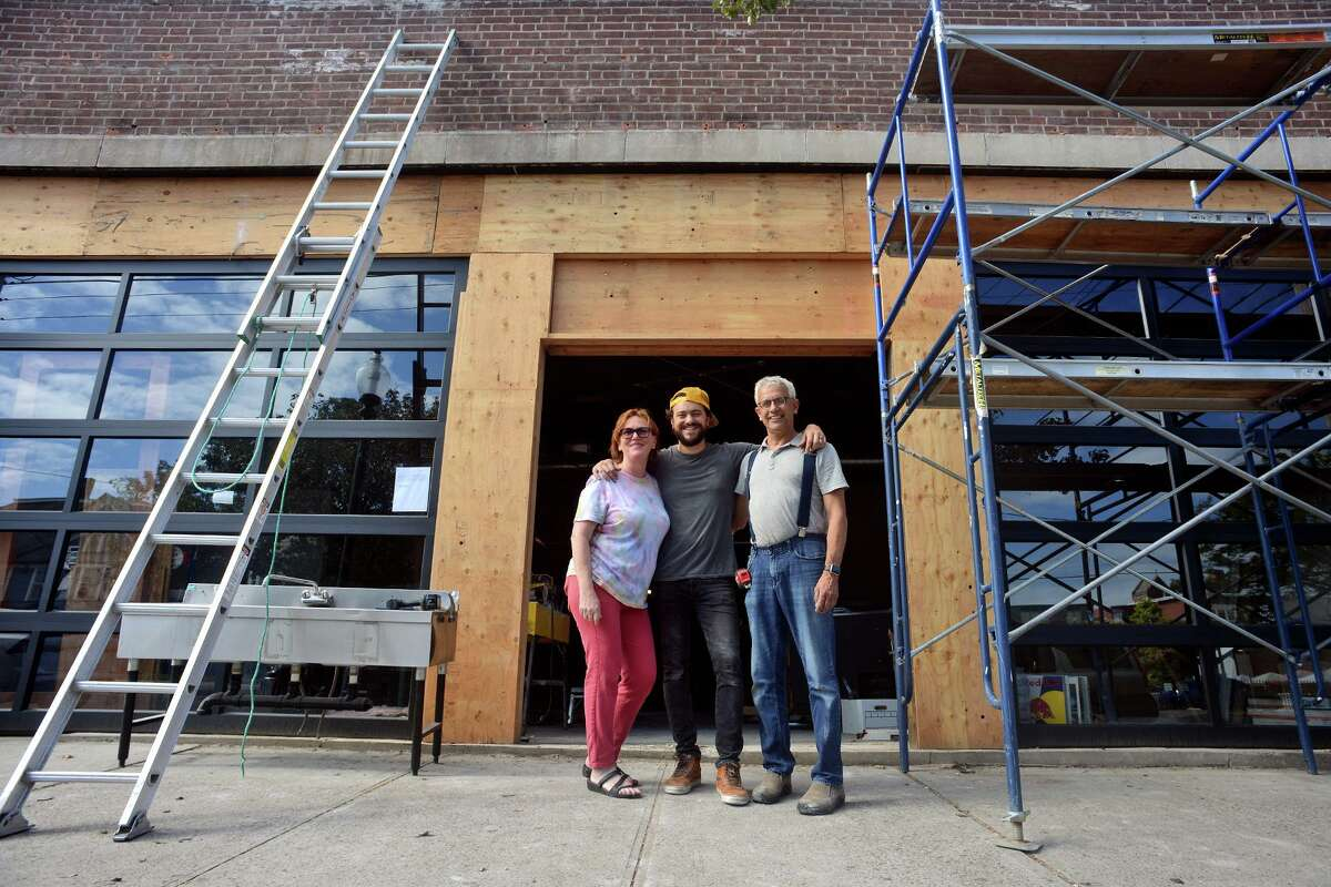 Owners Michele and Rick Torres stand with their son, John, center, the general manager of Park City Music Hall, currently under construction in the former Acoustic Café space, in Bridgeport, Conn. Oct. 6, 2021.