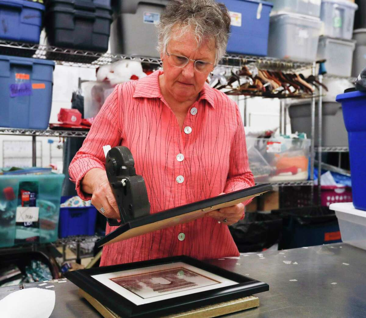 Karla Oubre, check recently donated items at the Interfaith of The Woodlands' Hand Me Up Shop, Thursday, Oct. 7, 2021, in Spring. The 10-year volunteer used various genealogy sites to help track down the families of several antique book donated to The Woodlands non-profit.
