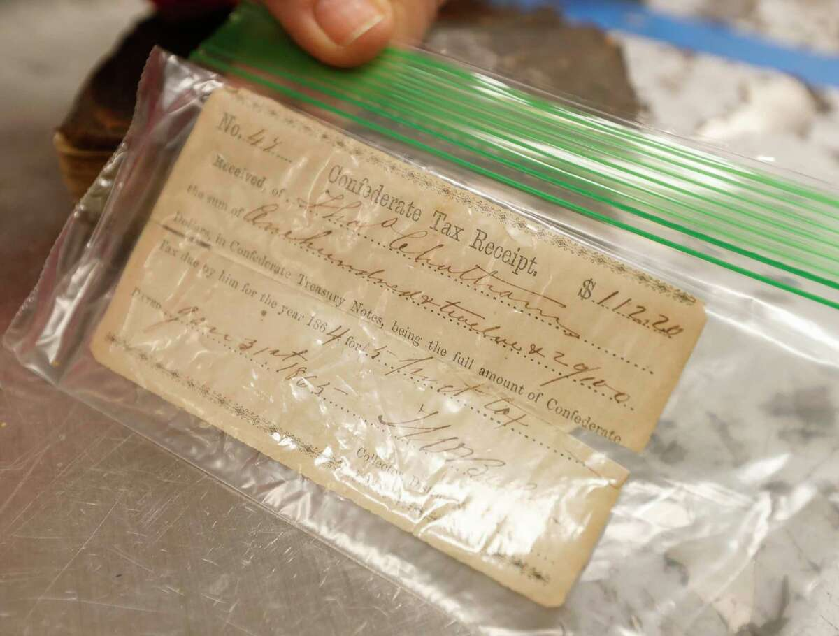 Karla Oubre, a 10-year volunteer of the Interfaith of The Woodlands' Hand Me Up Shop, shows a Confederate tax receipt recently found in a donated items, Thursday, Oct. 7, 2021, in Spring. The 10-year volunteer used various genealogy sites to help track down the families of several antique book and items donated to The Woodlands non-profit.