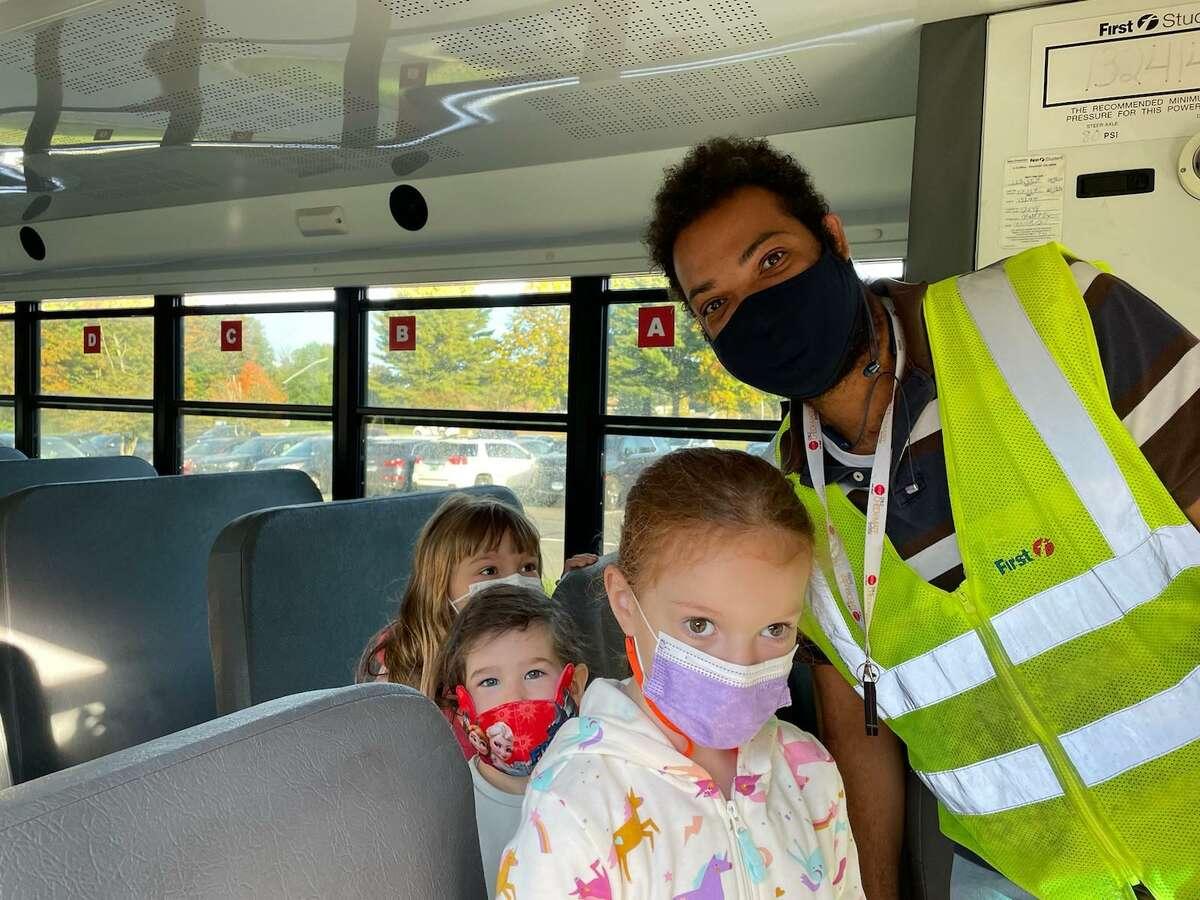 Ridgefield Public Schools bus driver Weberlecro Boisrond poses with Scotland Elementary School students Zoe Lazarin, Lily Emery and Katherine Mitev.