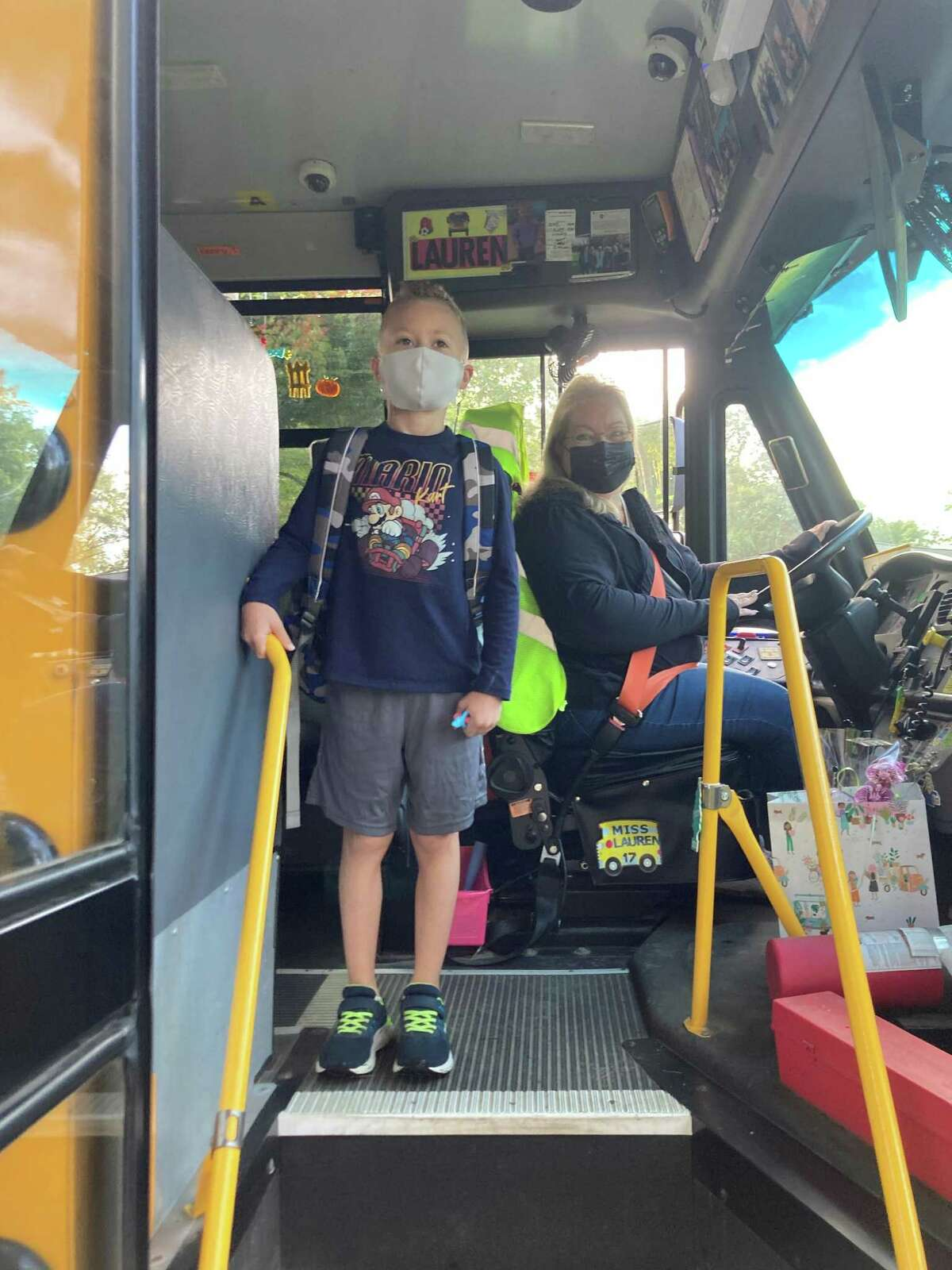 Ridgebury Elementary School second grader Gavin Landy boards the bus while posing for a picture with his bus driver, Lauren Sheridan Scavo.