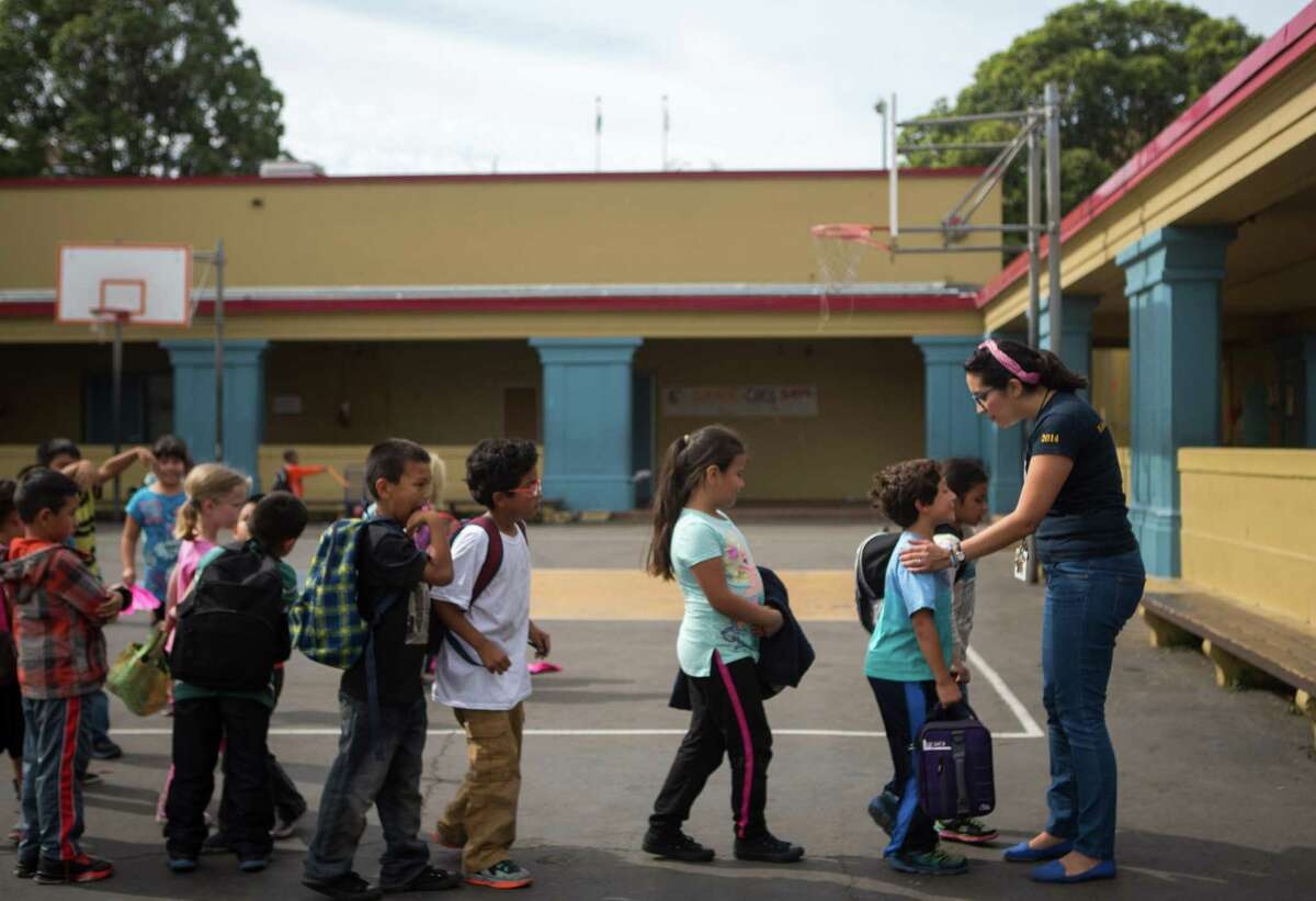 Maribel Chavez, a teacher at Buena Vista Horace Mann in the Mission district, lines up her students after lunchtime recess in San Francisco.