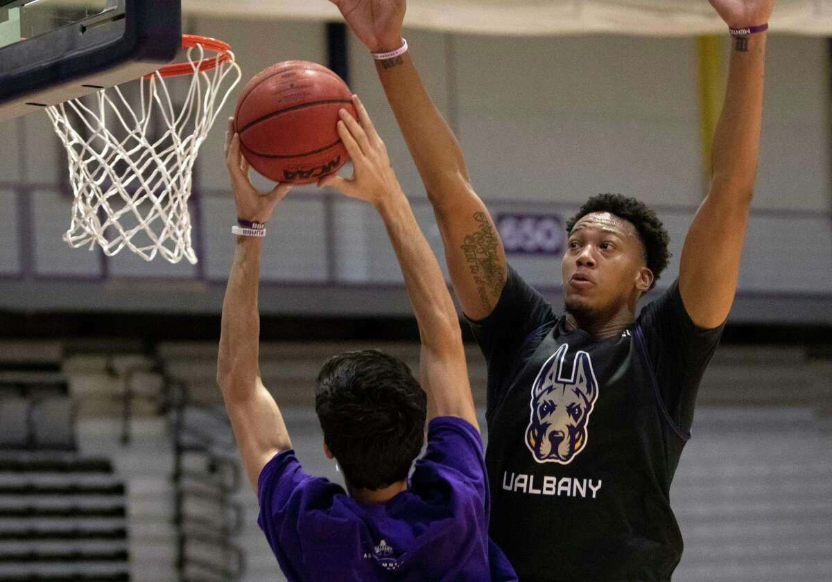 University at Albany basketball player Paul Newman, right, runs a defense drill during practice at the SEFCU Arena on Thursday, Oct, 7, 2021 in Albany, N.Y.