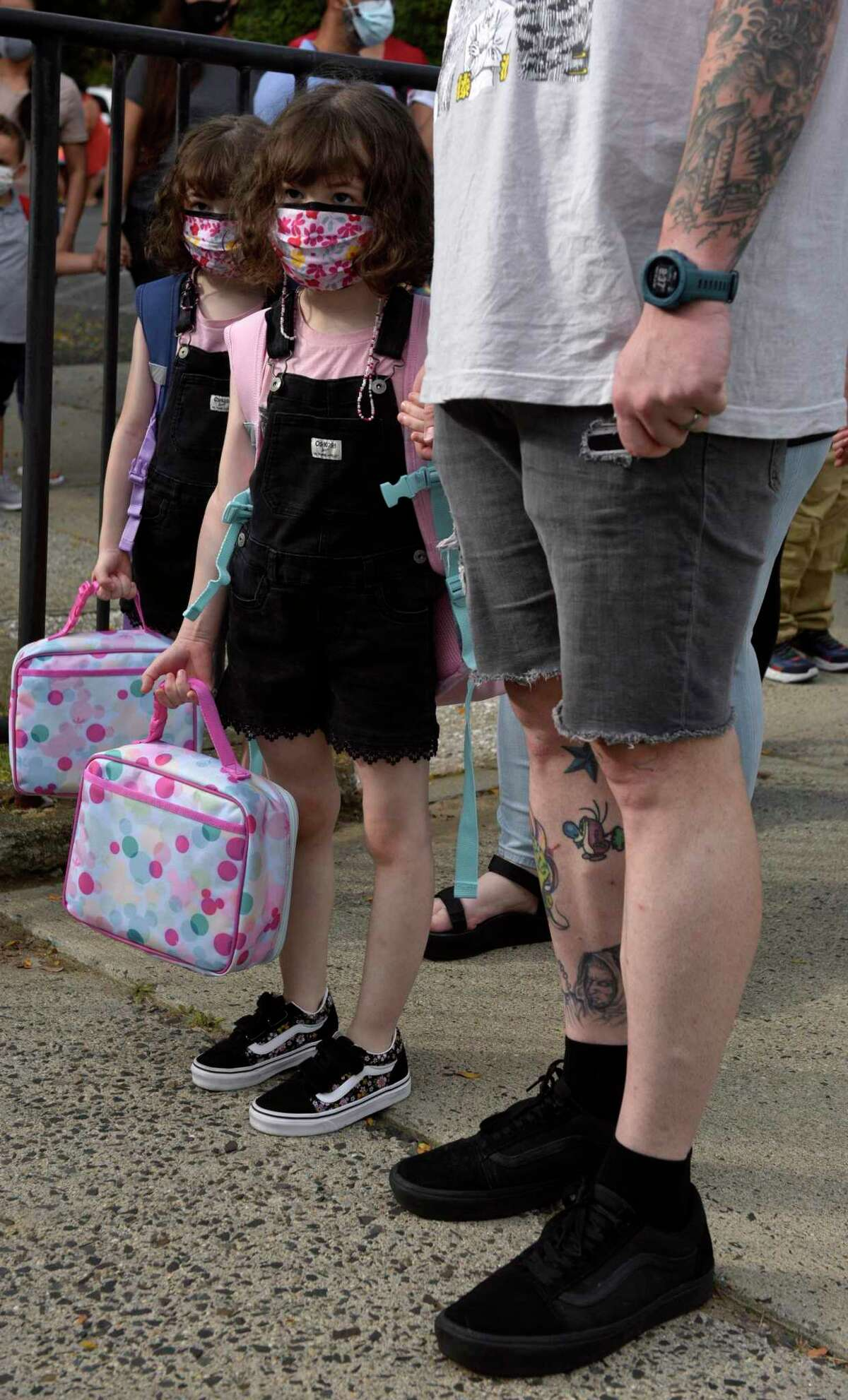 Twin sisters Lydia, left, and Lilith Copland stand with their father Ian Copland while being dropped off for the first day of kindergarten at the Danbury Primary Center in Brookfield. Monday, August 30, 2021, Brookfield, Conn. About 200 Danbury kindergartners are attending the school in Brookfield this year due to space constrictions in the elementary schools.