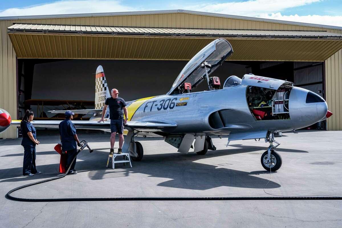 Greg Colyer (right) waits as Raj Gopal (center) and Sasha Larsen of Davis Flight Support refuel his 1940s-era T-33 jet trainer.