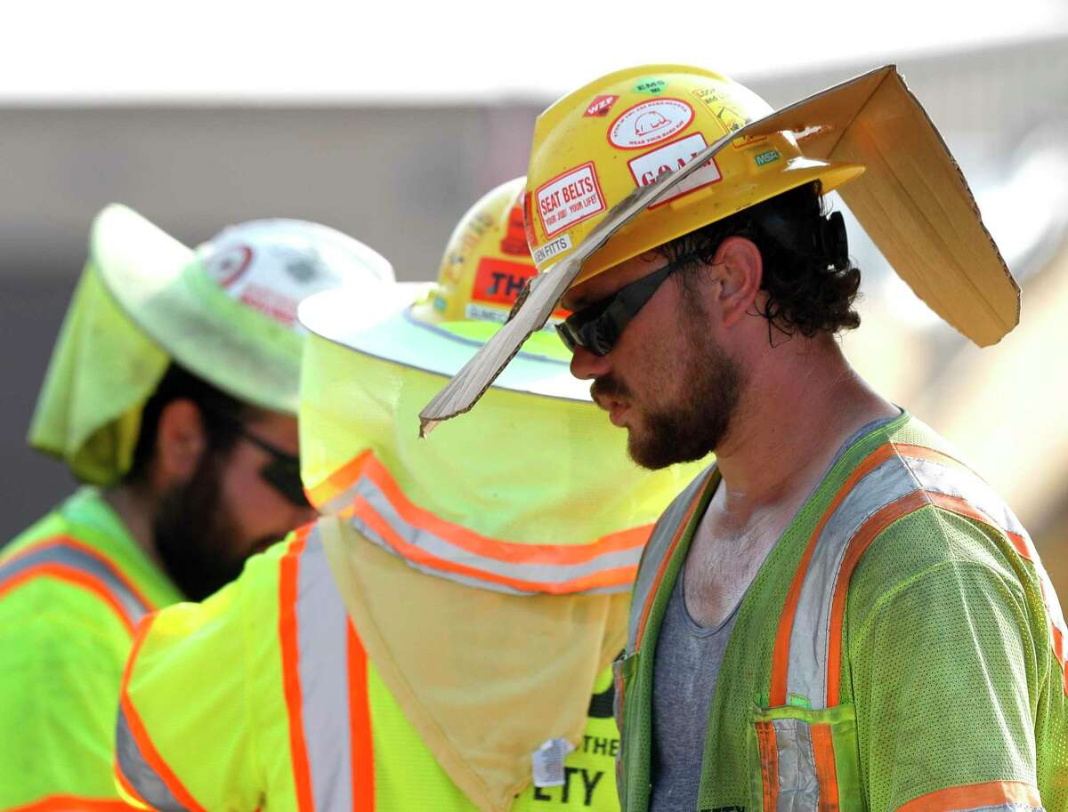"""Reagan Fitts wears a safety hat with a custom sun visor he made from a cardboard box while working on the Texas 242 construction project, Thursday, Sept. 2, 2021, in Conroe. """"Hey man, you do whatever works,"""" Fitts said. """"Especially in his heat. Brutal. No shade."""""""